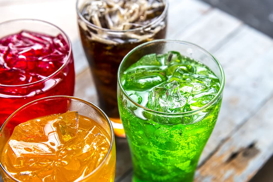 image of 4 clear glasses filled with different drinks (colors of each drink are red, orange/yellow, bright green, and brown/cola)