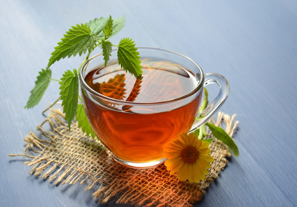 image of a clear mug filled with tea on a cloth coaster with a sunflower and green herb