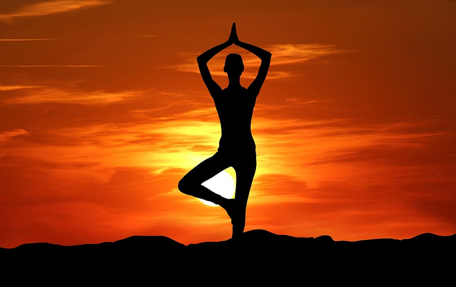 silhouette of a person in the tree pose in front of an orange and yellow sunset
