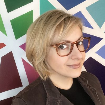 headshot of Mar Hicks in front of a geometric rainbow colored wall